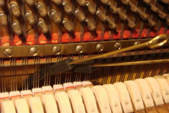 Muting of a three string string-set in the octave (7) below the highest (piano)