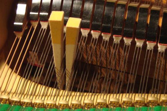 Muting of a three string string-set on a grand piano using two mutes