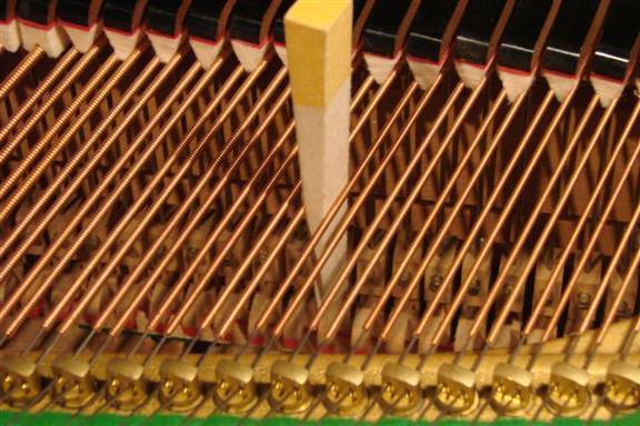 Muting of two two string string-set using a mute (grand piano)